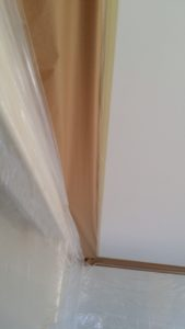 masking paper over a border to protect the drywall for a smooth painted border on a texture ceiling Texture King Calgary
